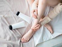 Όμορφη νέα γυναίκα που εφαρμόζει το λοσιόν σωμάτων στο σεντόνι Τοπ όψη Κενή ετικέτα για το μαρκάρισμα του προτύπου Φροντίδα δέρμα Στοκ Εικόνες