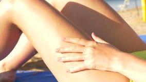 Όμορφη νέα γυναίκα που εφαρμόζει sunscreen στα πόδια στην παραλία HD απόθεμα βίντεο