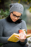 Όμορφη νέα γυναίκα που διαβάζει ένα βιβλίο και που πίνει το τσάι Στοκ εικόνα με δικαίωμα ελεύθερης χρήσης