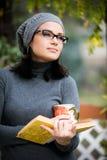 Όμορφη νέα γυναίκα που διαβάζει ένα βιβλίο και που πίνει το τσάι Στοκ Φωτογραφία
