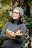 Όμορφη νέα γυναίκα που διαβάζει ένα βιβλίο και που πίνει το τσάι Στοκ Εικόνες