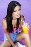Όμορφη νέα γυναίκα που κάθεται και που πίνει τον υγιή χυμό Στοκ φωτογραφία με δικαίωμα ελεύθερης χρήσης