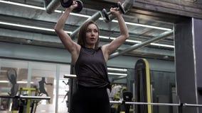 Όμορφη νέα γυναίκα που κάνει τις ασκήσεις για τους μυς απόθεμα βίντεο