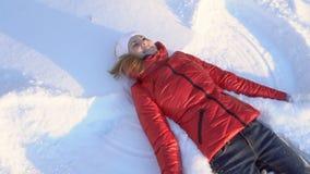 Όμορφη νέα γυναίκα που κάνει τον άγγελο χιονιού σε ένα χειμερινό πάρκο, που έχει την ανόητη διασκέδαση, χαμόγελο κίνηση αργή φιλμ μικρού μήκους