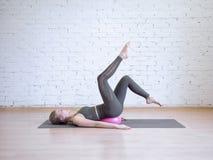 Όμορφη νέα γυναίκα που κάνει pilates workout με τη μικρή ρόδινη σφαίρα ικανότητας, άσκηση αψίδων ποδιών Εσωτερικό, υπόβαθρο σοφιτ στοκ φωτογραφία με δικαίωμα ελεύθερης χρήσης