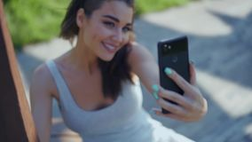 Όμορφη νέα γυναίκα που κάνει selfie στο πάρκο φιλμ μικρού μήκους
