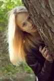 Όμορφη νέα γυναίκα που κοιτάζει από ένα δέντρο Στοκ Φωτογραφίες