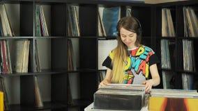Όμορφη νέα γυναίκα που κοιτάζει βιαστικά τα εκλεκτής ποιότητας αρχεία στο βινυλίου κατάστημα απόθεμα βίντεο