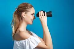 Όμορφη νέα γυναίκα που κοιτάζει μέσω των διοπτρών Στοκ Εικόνες