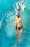 Όμορφη νέα γυναίκα που κολυμπά στο ύφος ύπτιου στοκ εικόνες με δικαίωμα ελεύθερης χρήσης