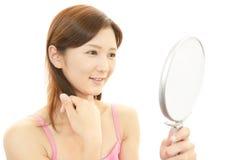 Όμορφη νέα γυναίκα που κρατά έναν καθρέφτη χεριών Στοκ Φωτογραφίες