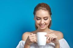 Όμορφη νέα γυναίκα που κρατά ένα άσπρο φλυτζάνι του ποτού και του χαμόγελου Στοκ Φωτογραφίες