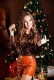 Όμορφη νέα γυναίκα που κρατά ένα κουδούνι στη Παραμονή Χριστουγέννων στοκ φωτογραφίες
