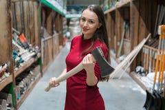 Όμορφη νέα γυναίκα που κρατά ένα ξύλινο αντιμετωπισμένο τσεκούρι Στοκ Φωτογραφίες