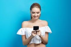Όμορφη νέα γυναίκα που κρατά ένα τηλέφωνο στο μπλε υπόβαθρο Στοκ Εικόνες