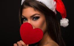 Όμορφη νέα γυναίκα που κρατά μια καρδιά μπροστά από το πρόσωπό της ενώ στοκ εικόνα