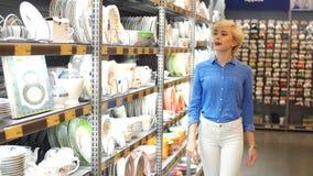 Όμορφη νέα γυναίκα που κρατά το άσπρο πιάτο, στεμένος στο διάδρομο με τα ράφια των αγαθών Καταναλωτισμός, αγορές φιλμ μικρού μήκους