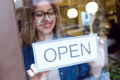 Όμορφη νέα γυναίκα που κρεμά το ανοικτό σημάδι στο κατάστημα Στοκ Εικόνες