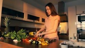 Όμορφη νέα γυναίκα που μαγειρεύει το φυτικό πιάτο στο σπίτι φιλμ μικρού μήκους