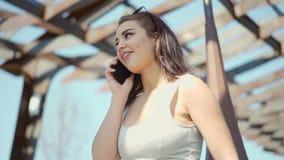 Όμορφη νέα γυναίκα που μιλά από το κινητό τηλέφωνο φιλμ μικρού μήκους