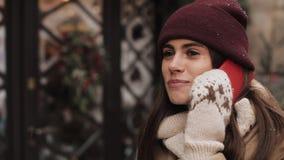 Όμορφη νέα γυναίκα που μιλά στο τηλέφωνο ενώ στέκεται στην οδό κοντά στην προθήκη Αυτή που γελά ανθίστε το χρονικό χειμώνα χιονιο απόθεμα βίντεο