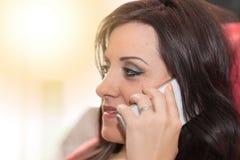 Όμορφη νέα γυναίκα που μιλά στο τηλέφωνο της Mobil στο σπίτι, ελαφριά επίδραση Στοκ εικόνα με δικαίωμα ελεύθερης χρήσης