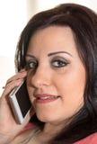 Όμορφη νέα γυναίκα που μιλά στο τηλέφωνο της Mobil στο σπίτι Στοκ Εικόνες