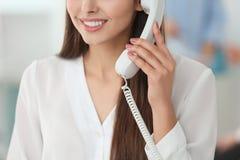 Όμορφη νέα γυναίκα που μιλά τηλεφωνικώς εργαζόμενος στην αρχή, κινηματογράφηση σε πρώτο πλάνο Στοκ Εικόνα