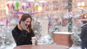 Όμορφη νέα γυναίκα που μιλά στο τηλέφωνο και το καυτό τσάι κατανάλωσης κατά τη διάρκεια της έκθεσης Χριστουγέννων απόθεμα βίντεο