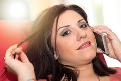 Όμορφη νέα γυναίκα που μιλά στο τηλέφωνο της Mobil στο σπίτι, ελαφριά επίδραση Στοκ Φωτογραφίες