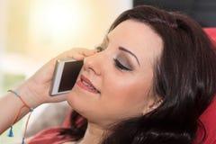 Όμορφη νέα γυναίκα που μιλά στο τηλέφωνο της Mobil στο σπίτι, ελαφριά επίδραση Στοκ Εικόνες