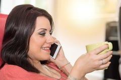 Όμορφη νέα γυναίκα που μιλά στο τηλέφωνο της Mobil στο σπίτι, ελαφριά επίδραση Στοκ φωτογραφίες με δικαίωμα ελεύθερης χρήσης