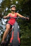 Όμορφη, νέα γυναίκα που οδηγά το ποδήλατο βουνών της στοκ εικόνα