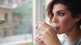 Όμορφη νέα γυναίκα που ονειρεύεται με το φλυτζάνι του καυτού καφέ πέρα από το παράθυρο όψη υψηλής διάλυσης eyedroppers κινηματογρ απόθεμα βίντεο