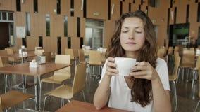 Όμορφη νέα γυναίκα που ονειρεύεται με το φλυτζάνι του καυτού καφέ πέρα από το παράθυρο απόθεμα βίντεο