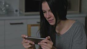 Όμορφη νέα γυναίκα που παίζει stealthily τα παιχνίδια στο κινητό τηλέφωνο στην κουζίνα τη νύχτα απόθεμα βίντεο