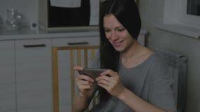 Όμορφη νέα γυναίκα που παίζει stealthily τα παιχνίδια στο κινητό τηλέφωνο στην κουζίνα τη νύχτα φιλμ μικρού μήκους