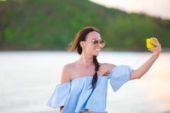 Όμορφη νέα γυναίκα που παίρνει μια μόνη φωτογραφία ο ίδιος στην τροπική παραλία Στοκ φωτογραφία με δικαίωμα ελεύθερης χρήσης