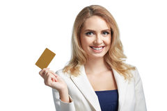 Όμορφη νέα γυναίκα που παρουσιάζει πιστωτική κάρτα και που χαμογελά στο ελαφρύ υπόβαθρο Στοκ Εικόνες