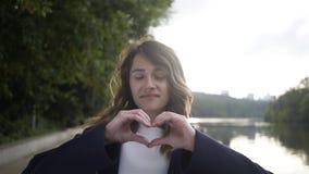 Όμορφη νέα γυναίκα που παρουσιάζει σημάδι καρδιών κοντά σε έναν ποταμό απόθεμα βίντεο