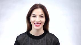 Όμορφη νέα γυναίκα που παρουσιάζει το χαμόγελο ή άσπρα δόντια της, που απομονώνεται στο άσπρο υπόβαθρο κίνηση αργή απόθεμα βίντεο