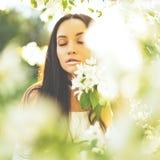 Όμορφη νέα γυναίκα που περιβάλλεται από τα λουλούδια του Apple-δέντρου Στοκ Εικόνα