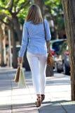 Όμορφη νέα γυναίκα που περπατά στην οδό ψωνίζοντας λευκή γυναίκα ποδιών έννοιας τσαντών ανασκόπησης Στοκ εικόνα με δικαίωμα ελεύθερης χρήσης
