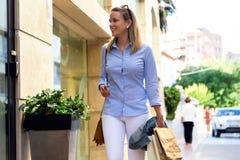 Όμορφη νέα γυναίκα που περπατά στην οδό ψωνίζοντας λευκή γυναίκα ποδιών έννοιας τσαντών ανασκόπησης Στοκ Εικόνες