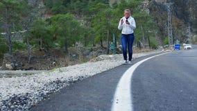 Όμορφη νέα γυναίκα που περπατά στο δρόμο που κρατά ένα έξυπνα τηλέφωνο και ένα χαμόγελο απόθεμα βίντεο