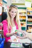 Όμορφη νέα γυναίκα που πληρώνει για τα παντοπωλεία της στο μετρητή στοκ εικόνα