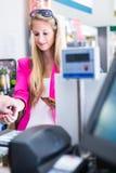 Όμορφη νέα γυναίκα που πληρώνει για τα παντοπωλεία της στο μετρητή στοκ εικόνες με δικαίωμα ελεύθερης χρήσης