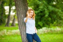 Όμορφη νέα γυναίκα που στέκεται δίπλα σε ένα δέντρο Στοκ Εικόνες