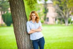 Όμορφη νέα γυναίκα που στέκεται δίπλα σε ένα δέντρο Στοκ εικόνες με δικαίωμα ελεύθερης χρήσης