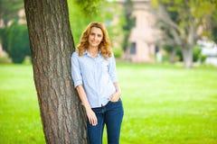 Όμορφη νέα γυναίκα που στέκεται δίπλα σε ένα δέντρο Στοκ φωτογραφίες με δικαίωμα ελεύθερης χρήσης